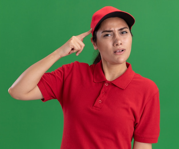 Ragazza confusa di consegna giovane che indossa l'uniforme e cappuccio che mette il dito sul tempio isolato sulla parete verde