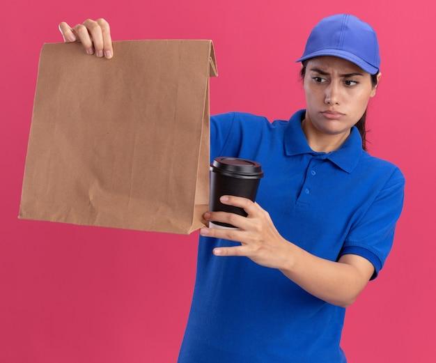 Смущенная молодая доставщица в униформе с кепкой, держащая и смотрящую на бумажный пакет продуктов с чашкой кофе, изолированной на розовой стене