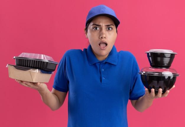 Смущенная молодая доставщица в униформе с кепкой, держащей контейнеры для еды, изолированные на розовой стене