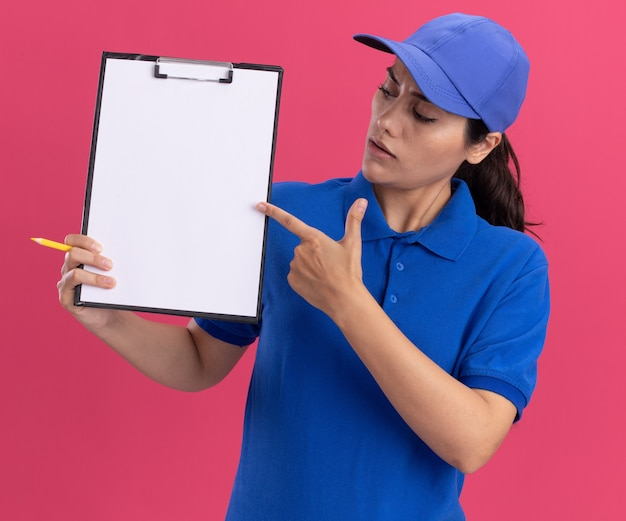 Confused young delivery girl wearing uniform with cap holding and points at clipboard isolated on pink wall