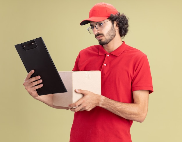 올리브 녹색 벽에 격리된 클립보드를 보고 있는 카드박스와 클립보드를 들고 안경을 쓴 모자를 쓴 빨간 유니폼을 입은 젊은 배달원