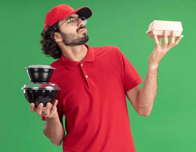 緑の壁に隔離された食品パッケージを見て、紙の食品パッケージと食品容器を保持している眼鏡をかけた赤い制服と帽子をかぶった混乱した若い配達人