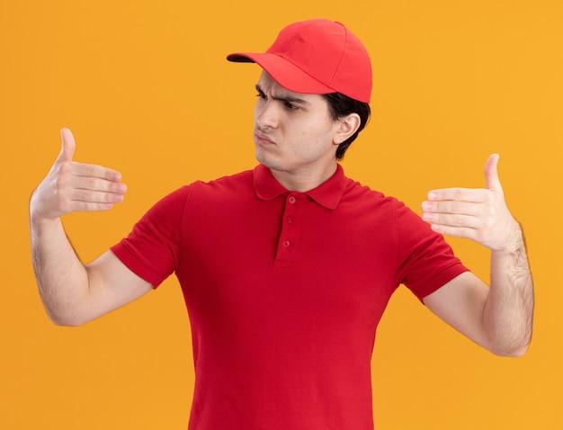 Confuso giovane fattorino in uniforme rossa e berretto finge di tenere qualcosa davanti a sé guardando la sua mano isolata sul muro arancione orange