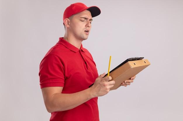 Смущенный молодой доставщик в униформе с кепкой, держащей буфер обмена с коробкой для пиццы - изолированный на белой стене