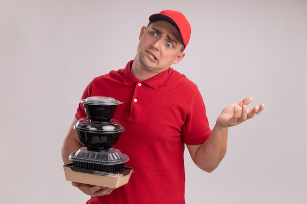 Confused young delivery man wearing uniform with cap holding food containers spreading hand isolated on white wall
