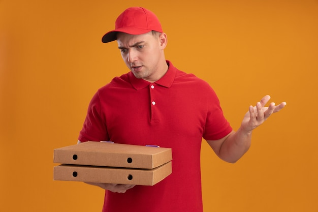Confused young delivery man wearing uniform with cap holding and looking at pizza boxes spreading hand isolated on orange wall