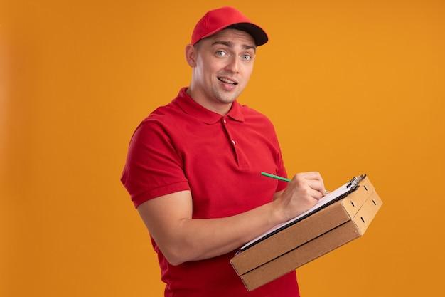 Смущенный молодой курьер в униформе с кепкой держит коробки для пиццы и что-то пишет в буфере обмена, изолированном на оранжевой стене