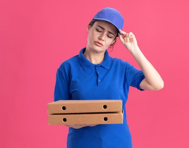 Смущенная молодая женщина-доставщик в униформе и кепке держит и смотрит на пакеты с пиццей, хватаясь за кепку