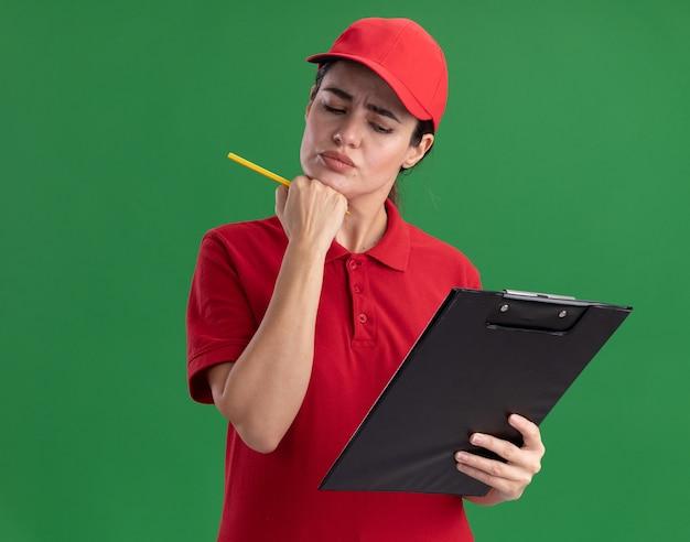 Confuso giovane donna di consegna in uniforme e cappuccio che tiene appunti e matita guardando appunti mettendo la mano sul mento isolato sul muro con spazio di copia