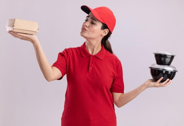 Confuso giovane donna delle consegne in uniforme e cappuccio che tiene un pacchetto di alimenti di carta e contenitori per alimenti che guardano un pacchetto di alimenti di carta isolato sul muro bianco