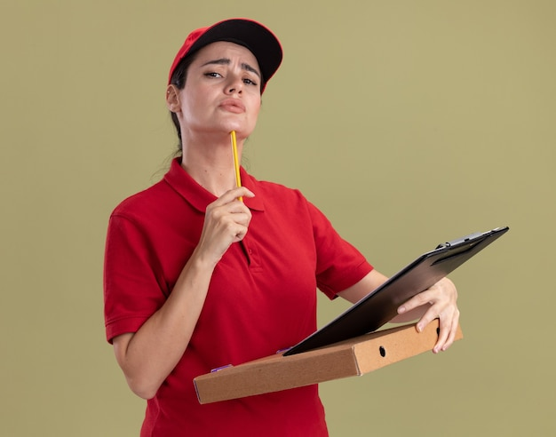 Confused young delivery woman in uniform and cap holding pizza package clipboard touching chin with pencil  isolated on olive green wall