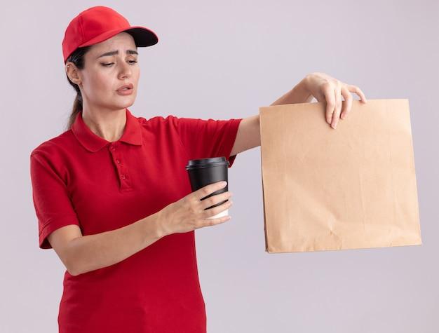 Confusa giovane donna delle consegne in uniforme e cappuccio che tiene una tazza di caffè in plastica e un pacchetto di carta guardando la tazza di caffè isolata sul muro bianco