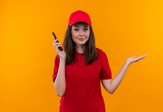 孤立したオレンジ色の壁に携帯電話を保持している赤い帽子に赤いtシャツを着て混乱している若い配達の女性