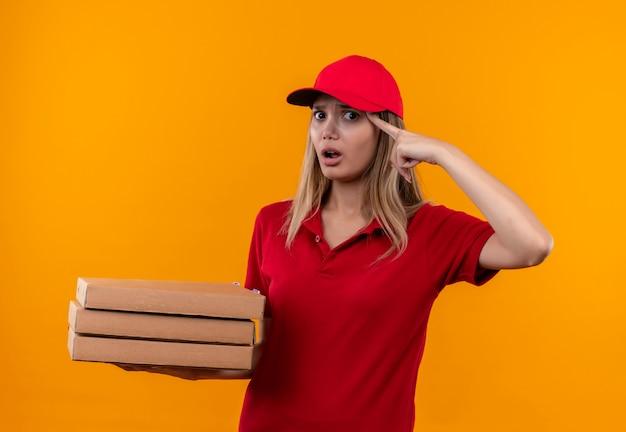 Confusa giovane donna delle consegne che indossa l'uniforme rossa e il cappuccio che tiene la scatola della pizza mettendo il dito sulla fronte
