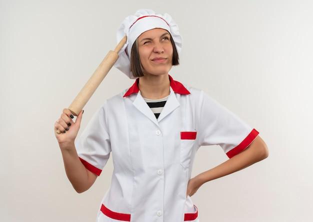 Giovane cuoco femminile confuso in uniforme del cuoco unico che tiene il mattarello e che mette la mano sulla vita che osserva in su isolato su bianco