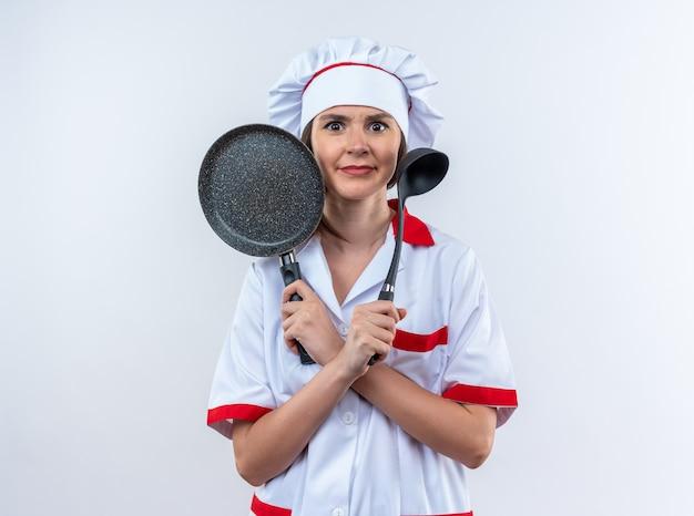 Смущенная молодая женщина-повар в униформе шеф-повара держит и пересекает сковороду с ковшом на белом фоне