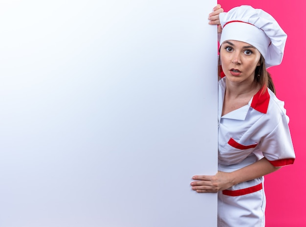 Смущенная молодая женщина-повар в униформе шеф-повара стоит за белой стеной, изолированной на розовом фоне с копией пространства