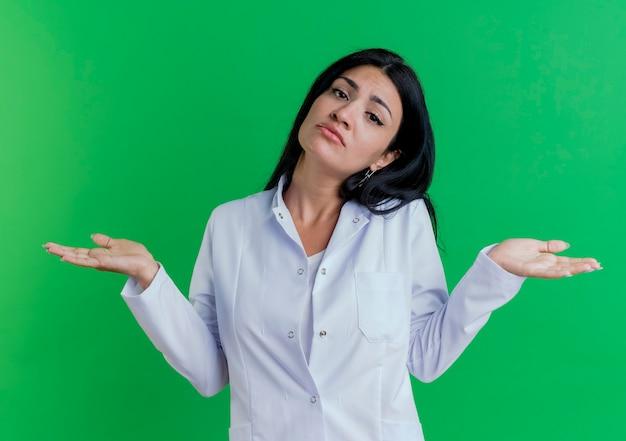 Giovane medico femminile confuso che porta veste medica che mostra le mani vuote isolate sulla parete verde