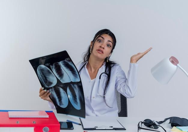 Giovane medico femminile confuso che indossa veste medica e stetoscopio seduto alla scrivania con strumenti medici che tengono il colpo dei raggi x che osserva che mostra la mano vuota isolata