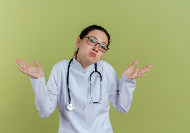 Giovane medico femminile confuso che indossa veste medica e stetoscopio con gli occhiali che diffondono le mani isolate
