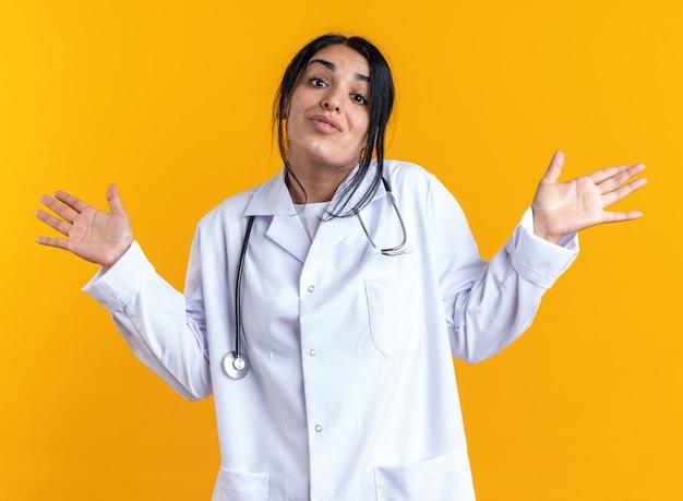 Giovane dottoressa confusa che indossa un abito medico con lo stetoscopio che spande le mani isolate sulla parete gialla