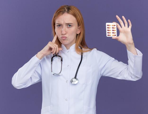 의료 가운과 청진기를 입은 혼란스러운 젊은 여성 생강 의사는 보라색 벽에 격리된 뺨을 만지는 전면에 의료 약 팩을 보여주고 있습니다.