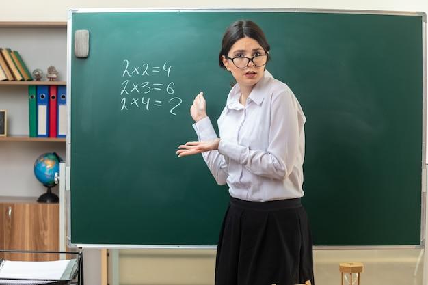 학교 도구와 함께 탁자 뒤에 서 있는 안경을 쓰고 교실에서 칠판에 손을 얹은 혼란스러운 젊은 여교사