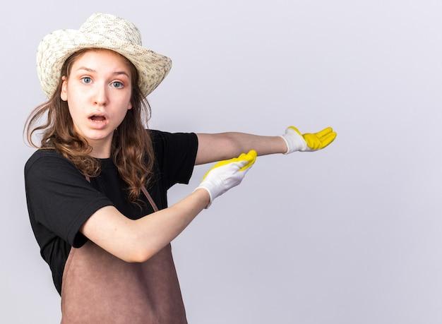 後ろに手袋をはめたガーデニング帽子をかぶった混乱した若い庭師