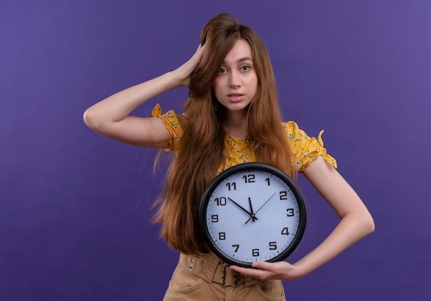 Confuso ragazza giovane azienda orologio e mettendo la mano sulla testa su uno spazio viola isolato