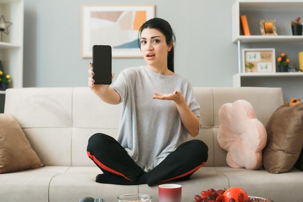 Ragazza confusa che tiene e indica con la mano il telefono seduto sul divano dietro il tavolino da caffè nel soggiorno