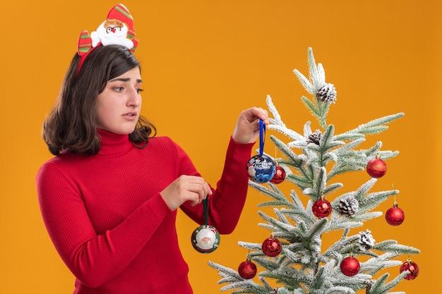 Смущенная молодая девушка в рождественском свитере с забавной повязкой на голову рядом с елкой на оранжевом фоне
