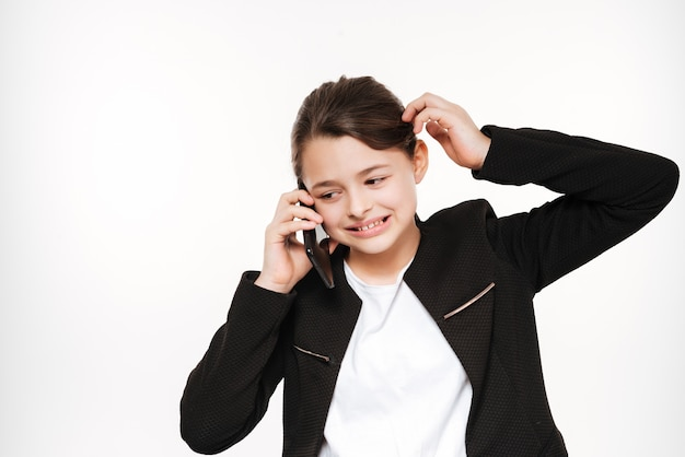 Confused young girl standing and talking by phone