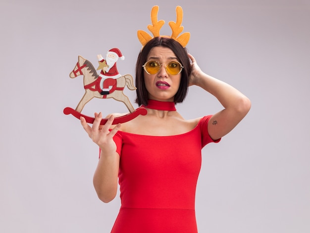 Confused young girl wearing reindeer antlers headband and glasses holding santa on rocking horse figurine looking at camera touching head isolated on white background