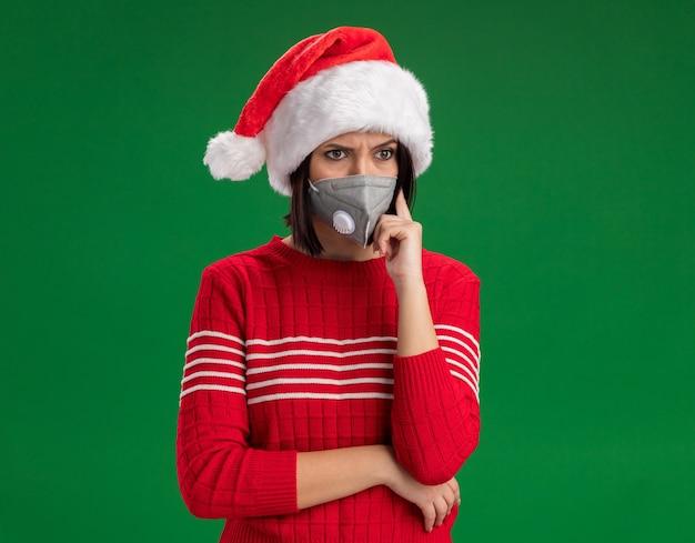 Смущенная молодая девушка в шляпе санта-клауса и защитной маске, смотрящей в сторону и делающая мысленный жест, изолирована на зеленом фоне с копией пространства