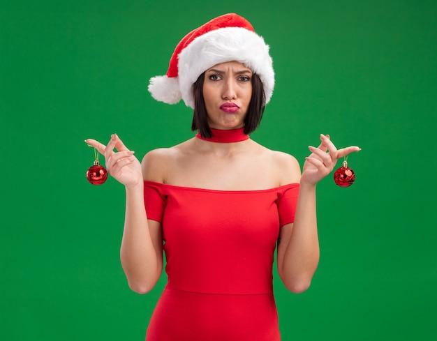Смущенная молодая девушка в шляпе санта-клауса с рождественскими шарами на зеленой стене