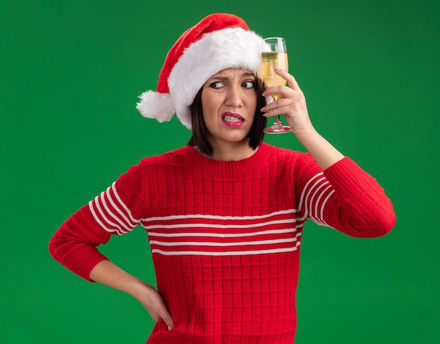 Confused young girl wearing santa hat holding glass of champagne touching head with it keeping hand on waist looking at side isolated on green background