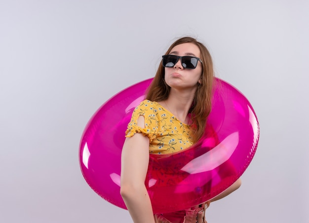 Смущенная молодая девушка в солнцезащитных очках и плавательное кольцо на изолированном белом пространстве с копией пространства