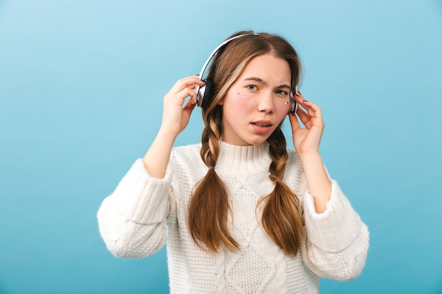 Confused young girl wearing winter clothes standing isolated, listening to music with headphones