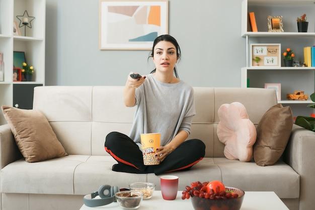 Ragazza confusa con il secchio di popcorn che tiene il telecomando della tv, seduta sul divano dietro il tavolino da caffè nel soggiorno