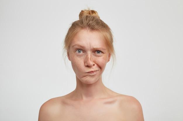 白い壁にポーズをとって、顔をしかめ、口をねじりながら、結び目でセクシーな髪を着ている混乱した若い緑色の目のきれいな女性