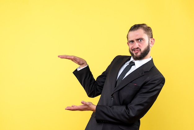 Confused young guy showing approximate size of something