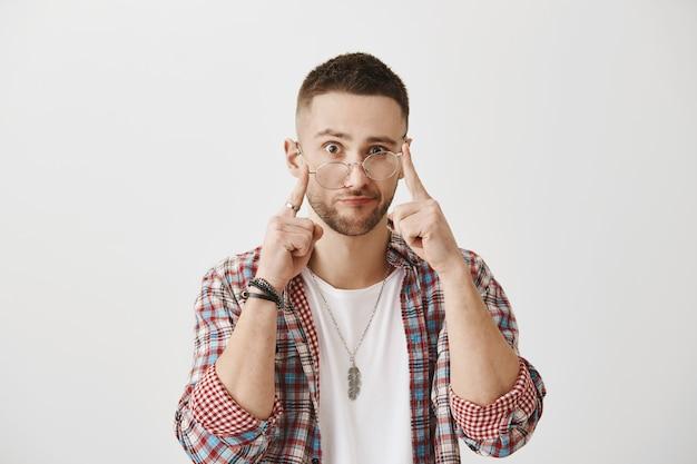 Путать молодой парень в очках позирует