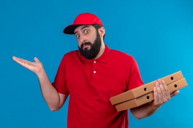 Confuso giovane uomo di consegna caucasico bello che indossa l'uniforme rossa e cappuccio che tiene le scatole per pizza e mostrando la mano vuota isolata sull'azzurro