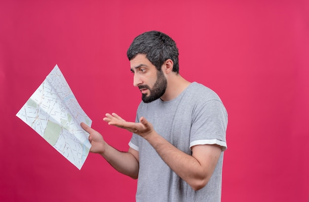 Confused young handsome caucasian traveler man holding and looking at map and showing empty hand isolated on pink  with copy space