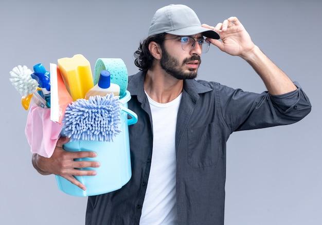 Смущенный молодой красивый уборщик в футболке и кепке, держащий ведро с чистящими средствами и держащий кепку, изолированную на белой стене