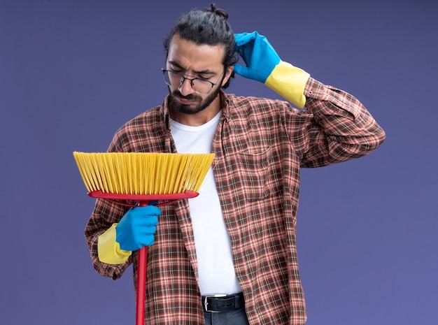 Смущенный молодой красивый уборщик в футболке и перчатках держит швабру, почесывая голову, изолированную на синей стене