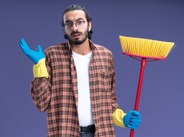 Confused young handsome cleaning guy wearing t-shirt and gloves holding mop spreading hand isolated on blue wall