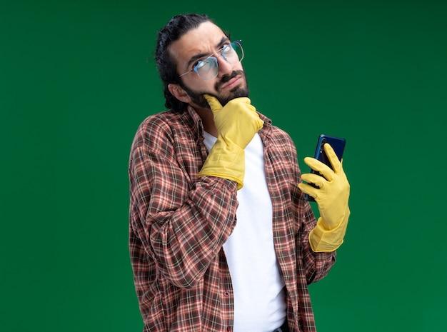Confuso giovane bel ragazzo delle pulizie che indossa t-shirt e guanti che tengono il telefono ha afferrato il mento isolato sulla parete verde
