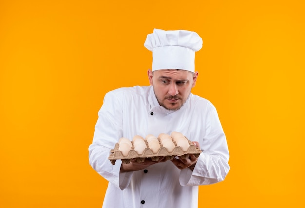 Confused young handsome cook in chef uniform holding carton of eggs looking at side isolated on orange wall