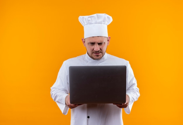 Смущенный молодой красивый повар в униформе шеф-повара, держащийся и смотрящий в ноутбук, изолированный на оранжевой стене